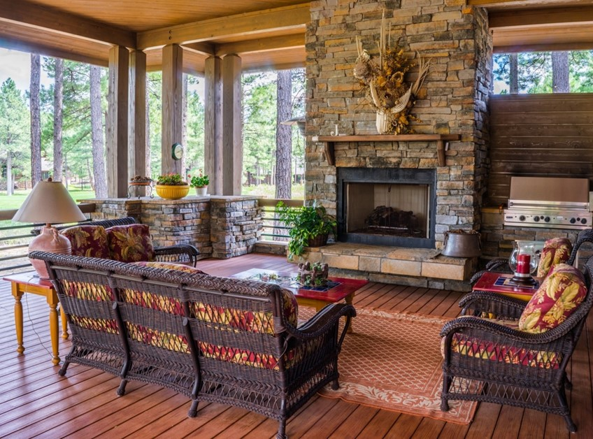 Stone and composite wood porch with railings, fireplace, and grill