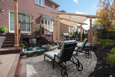 Stone patio with fountain and lounge chairs White brick patio with fountain and lounge chairs