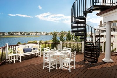 Open backyard dining area with a beautiful view and spiral staircase