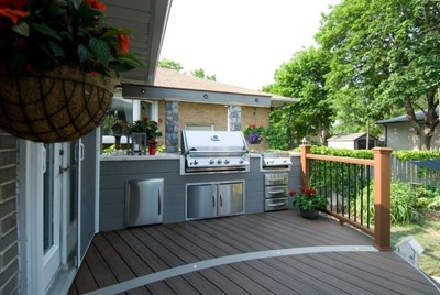 Stylish backyard kitchen with stainless steel appliances and grill