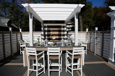 Outdoor kitchen design with bar seating under a white pergola