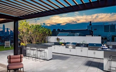 Full outdoor kitchen area with two stainless steel grills and bar seating