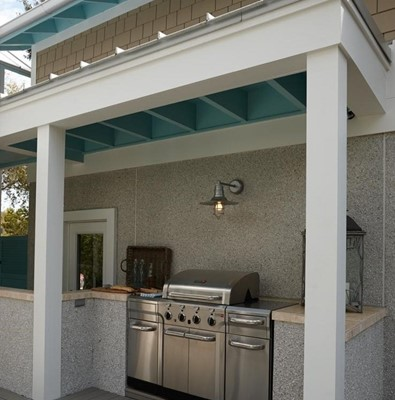 Small backyard kitchen set up with stainless steel grill under an overhang